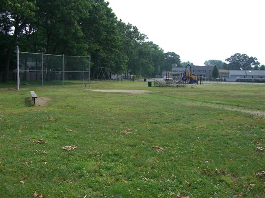 Baseball diamond with bench, backstop fence and small set of wooden bleachers