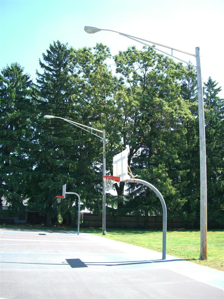 Basketball court with hoops and light poles